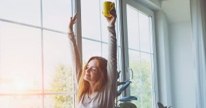 happy smiling young woman waking up, stretching, drinking coffee; blog: 10 ways to practice self-care at home