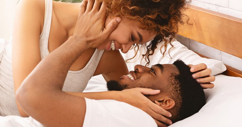 Good morning sex. Happy african-american man and woman kissing in bed, waking up in morning; blog: What You Should Know About Women's Intimate Health