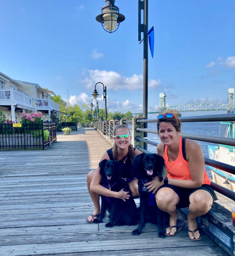 Dr. Pearce, her wife and their two dogs on a boardwalk